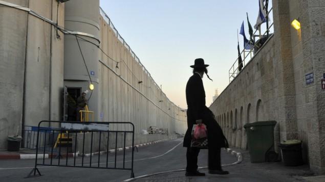 رجل يهودي متدين يسير بجانب الجدار الامني عند بيت لحمSerge Attal/Flash90/File