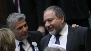 يائير لبيد ينظر مع وزير الخارجية السابق أفيغدور ليبرمان خلال الجلسة الافتتاحية للبرلمان إسرائيل ال19، الذي عقد في الكنيست  5 فبراير، 2013. Miriam Alster/Flash90