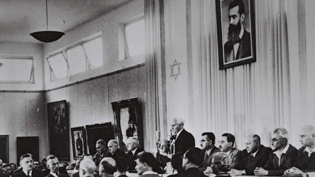 ديفيد بن غوريون، وأعضاء حكومته المؤقتة، يقرأ إعلان الاستقلال في متحف  تل أبيب  14 مايو، 1948  Israel Government Press Office