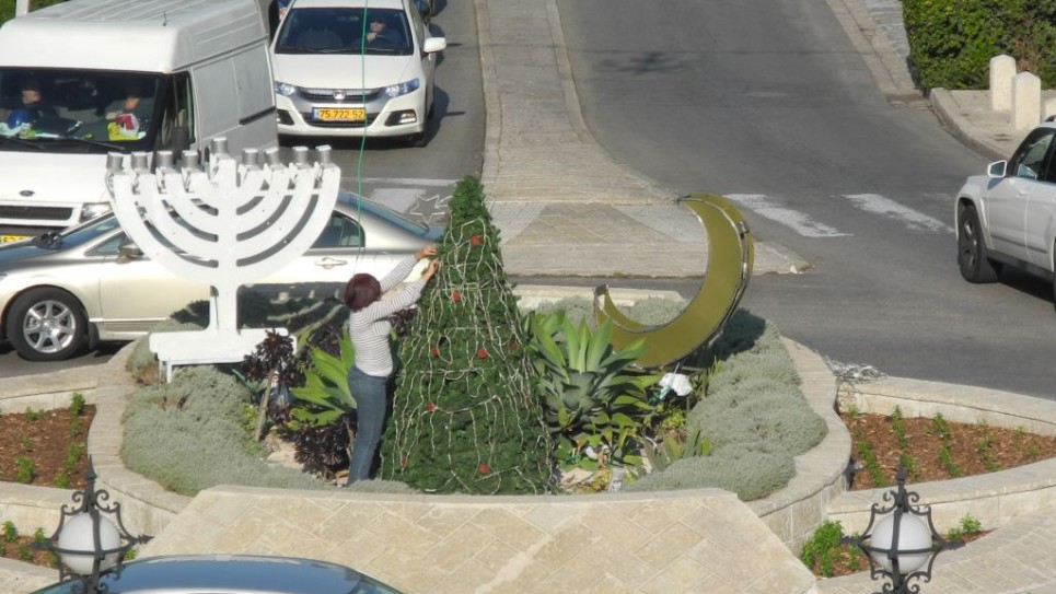 اللمسات الاخيرة على عرض يشمل شجرة الميلاد, هلال وشمعدان امام الحدائق البهائية في حيفا تحضيرا لاحتفالات عيد الاعياد. ديسمبر 2014 (طاقم تايمز أوف إسرائيل)