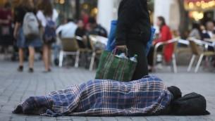 اشخاص يمرون بجانب رجل متشرد ينام في الشارع 10 نوفمبر 2010 (فلاش 90)