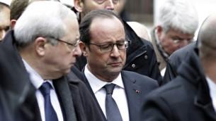 الرئيس الفرنسي فرانسوا هولاند (C) يصل  مقر الصحيفة الساخرة الفرنسية شارلي ابدو في باريس  7 يناير عام 2015، بعد ان اقتحم مسلحون المكاتب مما اسفر عن  أحد عشر قتيلا، بينهم اثنان من ضباط الشرطة، وفقا لمصادر قريبة من التحقيق AFP/KENZO TRIBOUILLARD