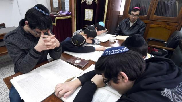 طلاب يهود تونسيون يدرسون نص ديني  13 يناير 2015، في المدرسة التي درس فيها يوآف حطاب - واحد من الضحايا اليهود الذين قتلوا خلال عملية احتجاز الرهائن في باريس الأسبوع الماضي AFP PHOTO / FETHI BELAID