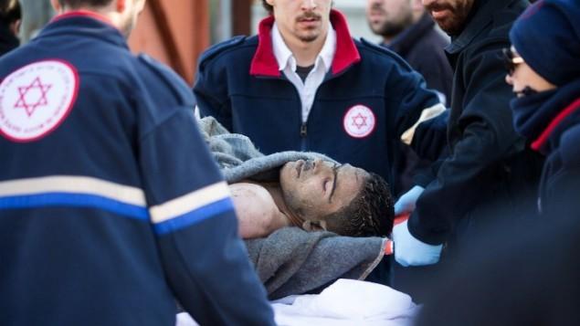 مسعفون ينقلون الرجل الفلسطيني الذي طعن وجرح أكثر من اثني عشر راكبا في هجوم على حافلة في تل أبيب في 21 يناير كانون الثاني 2015.AFP/OREN ZIV