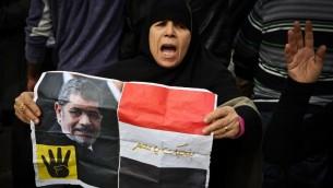 داعمة لتنظيم الاخوان المسلمين تحمل يافطة عليها صورة الرئيس المصري المخلوع محمد مرسي خلال مظاهرة في القاهرة، 24 يناير 2015 (MOHAMED EL-SHAHED / AFP)