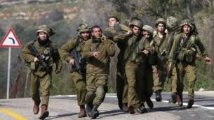 جنود الجيش  الإسرائيلي يحملون رفيقهم المصاب بعدان اصاب صاروخ مضاد للدبابات مركبة تابعة للجيش في منطقة تقع على الحدود مع لبنان  28 يناير كانون الثاني  2015 Jalaa Marey/AFP