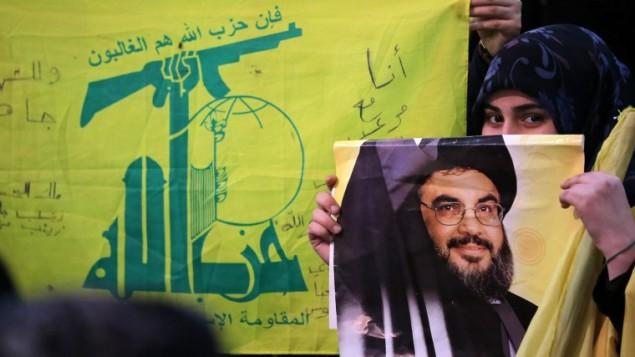 فتاة من انصار حزب الله تحمل ملصق صورة حسن نصر الله، رئيس الحركة  الشيعية في لبنان،  خلال  ث مباشر لخطابه  في الضاحية الجنوبية لبيروت . 30 يناير 2014 AFP PHOTO / JOSEPH EID