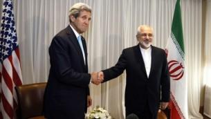وزير الخارجية الإيراني محمد جواد ظريف يصافح وزير الخارجية الأمريكي جون كيري في جينيف، 14 يناير 2015 (AFP/POOL/RICK WILKING)