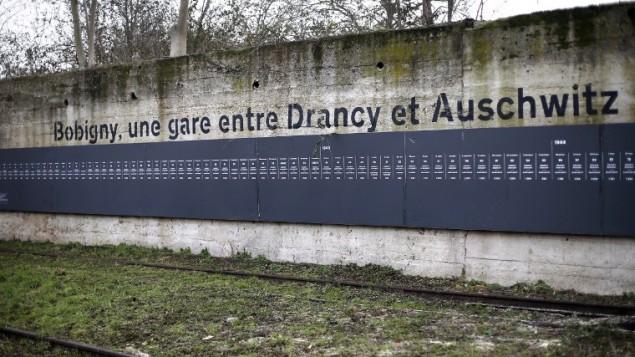 لوحة تذكارية بالقرب من محطة القطار السابقة في بوبيني، شمال شرق باريس، التي استعملت لترحيل اليهود إلى معسكر الموت أوشفيتز-بيركيناو  ، 27 يناير 2015 اليوم الدولي لإحياء ذكرى المحرقة والذكرى ال70 ل تحرير معسكر الموت أوشفيتز-بيركيناو. AFP PHOTO / THOMAS SAMSON