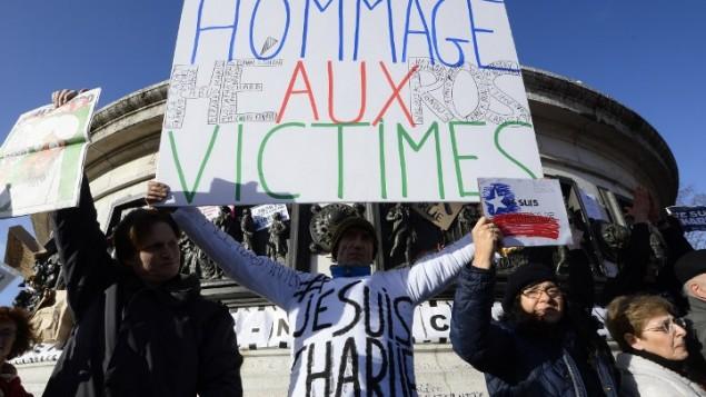"""لافتة مكتوب عليها """"تكريم للضحايا-الابطال""""  في ميدان الجمهورية (ساحة الجمهورية) في باريس قبل بدء مسيرة الوحدة """"المسيرة الجمهورية"""" 11 يناير  AFP PHOTO / BERTRAND GUAY"""