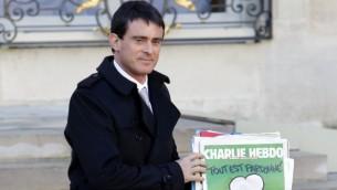 رئيس الوزراء الفرنسي مانويل فالس، والطبعة الأخيرة من المجلة الساخرة شارلي ابدو الفرنسية، يترك قصر الاليزيه بعد الاجتماع الاسبوعي للحكومة  14 يناير 2015 في باريس AFP/PATRICK KOVARIK