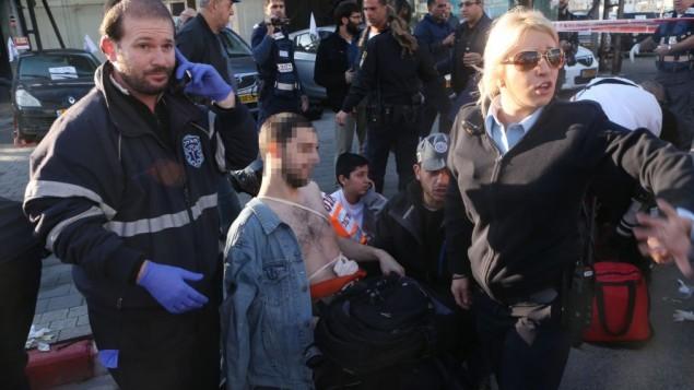 المسعفون والشرطة يقومون بإخلاء رجل اسرائيلي الذي أصيب بجروح في هجوم طعن على  الحافلة رقم 40 في تل أبيب  21 يناير، 2015  (فلاش 90)