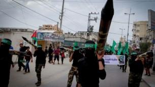 اعضاء ملثمون من حركة حماس يعرضون صواريخ خلال مسيرة في مركز قطاع غزة، 12 ديسمبر 2014 ( Abed Rahim Khatib / Flash90)