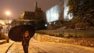 فتاة صغيرة  مع مظلة بالقرب من أسوار البلدة القديمة في القدس خلال العاصفة  07 يناير كانون الثاني عام 2015  (فلاش 90)