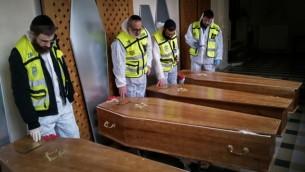 المتطوعون الطبيون مع الصناديق الأربعة للضحايا اليهود للهجوم ارهابي باريس قبل مراسيم الدفن وفقا للشريعة اليهودية 12 يناير 2015  (فلاش 90)