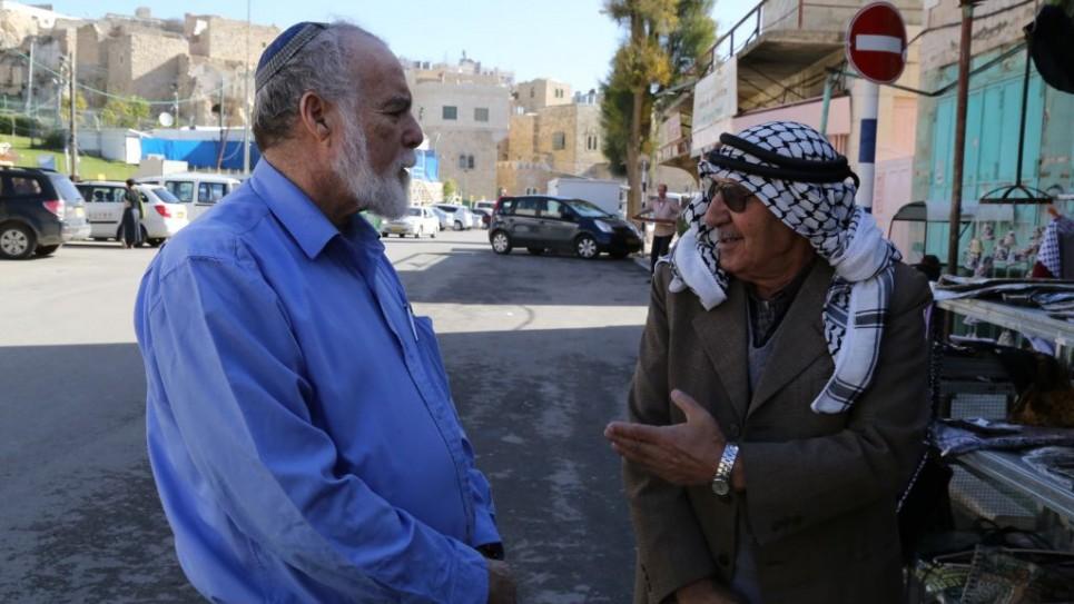 رجل عربي ورجل يهودي امام الحرم الابراهيمي في الخليل 10 ديسمبر 2015 (فلاش 90)