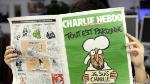 رجل في غرفة الأخبار في باريس، يقرأ العدد الأخير من أسبوعية الفرنسية الساخرة شارلي ابدو 13 يناير 2015   AFP/Bertrand Guay