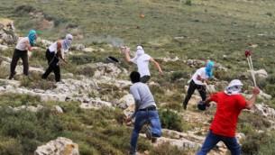 صورة توضيحية لمستوطنين ملثمين يتبادلون رمي الحجارة مع فلسطينيين في الضفة الغربية 3 مايو 2013 (Issam Rimawi/FLASH90)