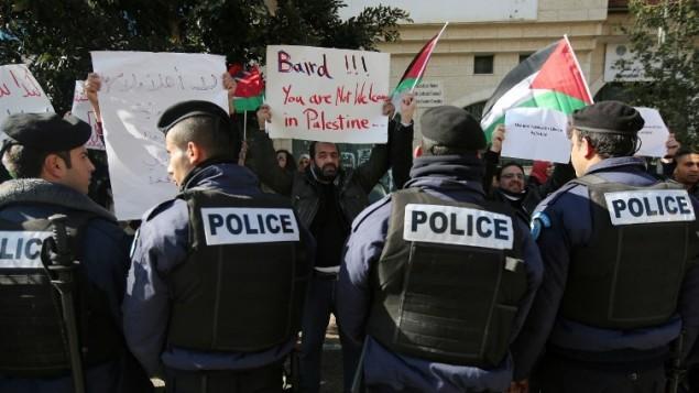متظاهرون فلسطينيون يحملون لافتات قبل اجتماع بين وزير الشؤون الخارجية للسلطة الفلسطينية رياض المالكي ونظيره الكندي جون بيرد 18 يناير 2015، رام الله. (أ ف ب / عباس المومني)