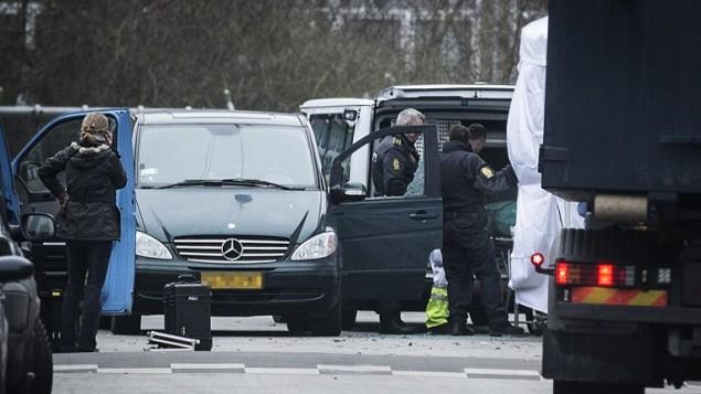 عناصر الشرطة تخلي جثمان رجلا يُعتقد بأنه منفذ هجومي إطلاق النار في العاصمة الدنماركية من موقع سقوطه، 15 فبراير 2015 (CLAUS BJORN LARSEN / AFP)