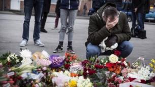 رجل يبكي امام اكاليل الزهور لذكرى ضحايا الهجوم على المركز الثقافي في كوبنهاغن، 15 فبراير 2015 (CLAUS BJORN LARSEN / AFP)