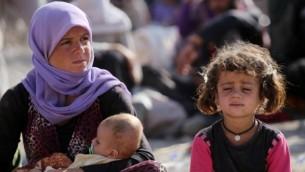 وقالت امرأة عراقية اليزيدية تجلس مع أطفالها في مخيم لاجئين بالقرب من نهر دجلة في محافظة دهوك غرب كردستان، حيث لجأوا بعد فرارهم من تقدم  الدولة الإسلامية في العراق 13 أغسطس، 2014  AFP/AHMAD AL-RUBAYE