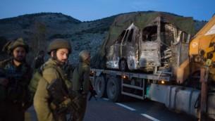 جنود اسرائيليون ينقلون مركبة محروقة من موقع هجوم حزب الله في مزارع شبعا في 28 يناير 2015 (AFP/MENAHEM KAHANA)