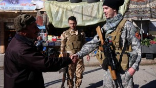 الاميركي بريت رويالز، 28، الذي يحارب بصفوف الفصيل المسيحي دويخ ناوشا بشمال العراق يصافح رجلا في بلدة القوش (SAFIN HAMED / AFP)