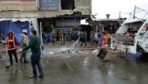 العراقيون ينظفون الشوارع بعد انفجار في مطعم في بغداد الجديدة، 7 فبراير 2015 (SABAH ARAR / AFP)