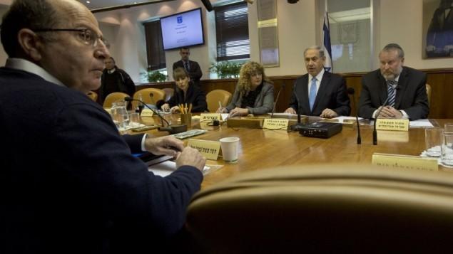 رئيس الوزراء بنيامين نتنياهو يجلس امام وزير الدفاع موشيه يعالون بينما يدير جلسة الحكومة الاسبوعية في مكتبه في القدس، 8 فبراير 2015 (AFP/POOL/SEBASTIAN SCHEINER)