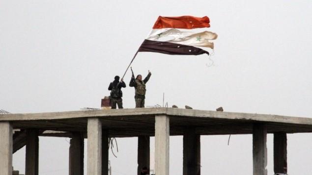 قوات النظام تلوح بالعلم السوري في دير العدس في مقاطعة درعا بعد طرد قوات الأسد، بدعم من حزب الله وإيران، المعارضين منها، 11 فبراير 2015 (STR / AFP)