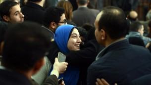 جيهان راشد، زوجة صحفي الجزيرة المصري باهر محمد، تعانق شخصا بعد قرار المحكمة الإفراج عن زوجها (MOHAMED EL-SHAHED / AFP)