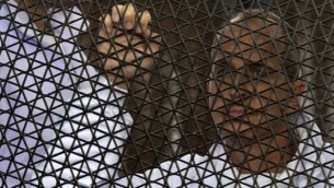 5 مارس عام 2014، الصحفي الاسترالي بيتر غرسته من قناة الجزيرة يقف داخل قفص المتهمين أثناء محاكمته. رحلت مصر غرسته إلى أستراليا في 1 فبراير 2015، بعد احتجازه لأكثر من 400 يوم AFP PHOTO / KHALED DESOUKI