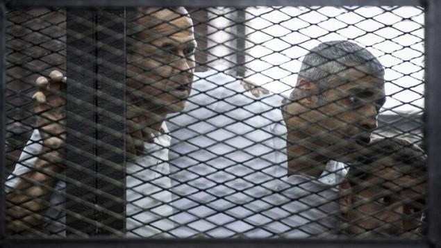 23 يونيو 2014 للصحافي في قناة الجزيرة القناة الاسترالي بيتر غريست (L) وزملاؤه، الكندي المصري محمد فاضل فهمي (C) والمصري باهر محمد،  داخل قفص المتهمين خلال المحاكمة AFP PHOTO / KHALED DESOUKI