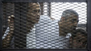 صورة التقطت في محطة الشرطة بالقرب من سجن طوره في القاهرة، تظهر صحفيي الجزيرة بيتر غريست الاسترالي (يسار) محمد فهمي الكندي-مصري وباهر محمد المصري (يمين)، 23 يونيو 2014 (KHALED DESOUKI / AFP)