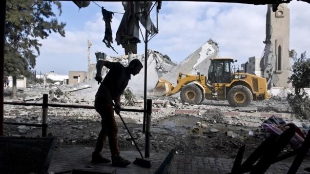 رجل فلسطيني يكنس مدخل بيته الذي تضرر بعد قصف مسجد قريب منه في بيت لاهيا، 25 اغسطس 2014 (AFP Photo/Roberto Schmidt)