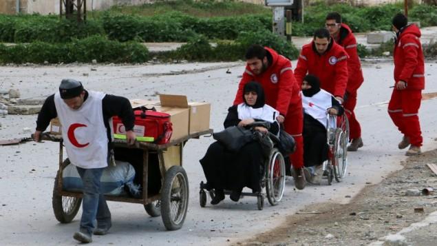 عاملو الهلال الأحمر ينقلون مصابين من مناطق المعارضة الى مناطق النظام في مدينة حلب السورية، 4 فبراير 2015 (BARAA AL-HALABI / AFP)