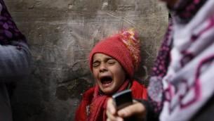 صبي فلسطيني يبكي أثناء تشييع جنازة طفل عمره 9 اشهر، بعد وفاته في حريق جراء تماس كهربائي، في مدرسة للامم المتحدة تستخدم كمأوى للفلسطينيين الذين دمرت منازلهم  في القصف الإسرائيلي  صيف 2014،  بيت حانون ، غزة 17 فبراير، 2015. AFP PHOTO / MOHAMMED ABED