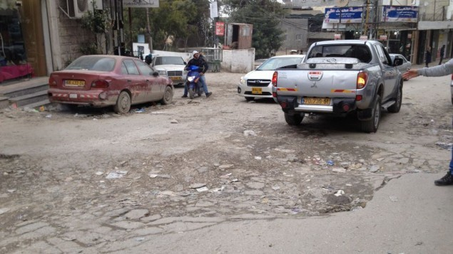 حفرة عميقة تعرقل السير في الشارع الرئيسي في مخيم شعفاط في القدس الشرقية الواقع خارج الجدار، 26 يناير 2015 (Elhanan Miller/Times of Israel)