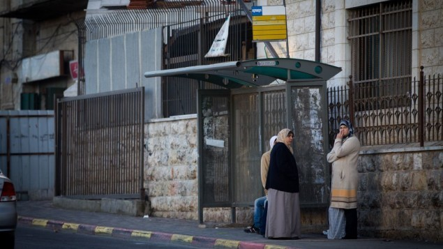 نساء فلسطينيات تنتظرن في محطة للحافلات في حي شعفاط بالقدس الشرقية، في 16 ديسمبر 2014 (فلاش 90)