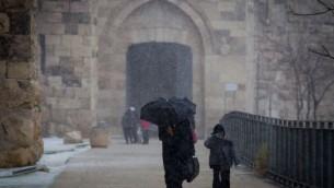 اشخاص تمشي في البلدة القديمة في القدس مع تساقط الثلج، 7 يناير 2015 (Miriam Alster/FLASH90)