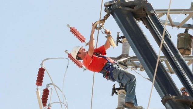 عامل صيانة في شركة الكهرباء يعمل على خطوط الكهرباء (Roni Schutzer/Flash90)
