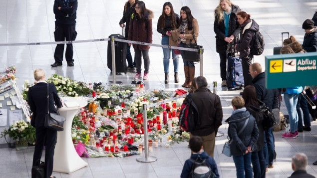 أشخاص يضعون  الرسائل والشموع  وأكاليل الزهور عند نصب تذكاري لضحايا طائرة جيرمان وينغز المنكوبة التي تحطمت في جبال الألب الفرنسية في مطار دوسلدورف في 28 مارس، 2015. (AFP/DPA/MARIUS BECKER)