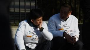 اثنين من اقرباء المفقودين في حادث اختفاء الطائرة الماليزية في مظاهرة امام السفارة الماليزية في بكين، 8 مارس 2015 (GREG BAKER / AFP)