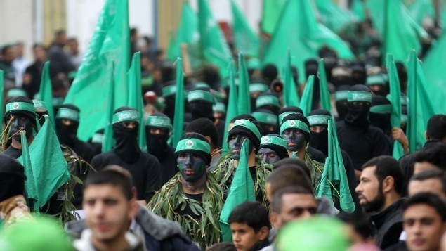 نشطاء فلسطينيون في كتائب عز الدين القسام، الجناح العسكري لحركة حماس، خلال مسيرة لإحياء الذكري ال27 لتأسيس الحركة، في مخيم النصيرات للاجئين وسط غزة في 12 ديسمبر، 2014. ( AFP/ SAID KHATIB)