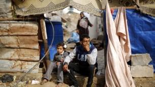 رجل وطفلة فلسطينيين امام منزلهم المدمر في بيت حانون شمال قطاع غزة، 4 مارس 2015 (MOHAMMED ABED / AFP)