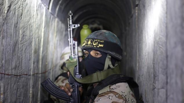 مسلحون فلسطينيون من الجناح المسلح للجهاد الإسلامي، سرايا القدس، داخل نفق  يُستخدم لنقل الصواريخ والقذائف استعدادا للصراع القادم مع إسرائيل، خلال مشاركتهم في تدريب عسكري جنوب قطاع غزة في 3 مارس، 2015. (AFP/MAHMUD HAMS)