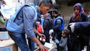 لاجئون فلسطينيون ينتظرون في مخيم اليرموك جنوب دمشق للحصول على المساعدات التي توزعها وكالة الامم المتحدة لاغاثة وتشغيل اللاجئيين الفلسطينيين (اونروا)  10 مارس 2015  AFP PHOTO / YOUSSEF KARWASHAN