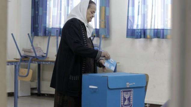 امرأة عربية في اسرائيل تضع صوتها في صندوق اقتراع في حيفا، 17 مارس 2015 (AFP PHOTO / AHMAD GHARABLI)