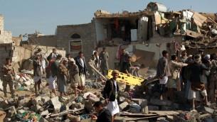 البحث عن الناجين بعد غارة سعودية بالقرب من مطار صنعاء في اليمن، 26 مارس 2015 (MOHAMMED HUWAIS / AFP)